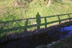 男人或妇女在桥梁,他们的在一个草甸的阴影秋天站立小河的银行的 库存图片