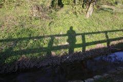 男人或妇女在桥梁,他们的在一个草甸的阴影秋天站立小河的银行的 免版税库存图片