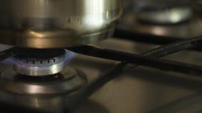 男人或妇女点燃在自动电燃烧的火在先进的煤气炉并且投入它金属平底锅 ? 免版税图库摄影