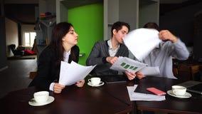 男人的坚苦工作天和妇女、同事和与工商业票据一起使用,在桌上与小配件在时髦的办公室 股票录像