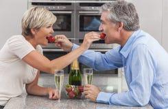 男人&妇女夫妇厨房草莓香宾 免版税库存图片