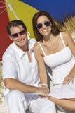 男人&妇女夫妇在海滩的多色的伞下 免版税库存图片
