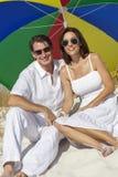 男人&妇女夫妇在海滩的多色的伞下 免版税库存照片
