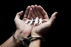 男囚犯扣上了手铐与家庭纸折叠 免版税库存图片