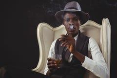 男女不分的人抽烟的雪茄,当时,当坐椅子时 免版税库存图片