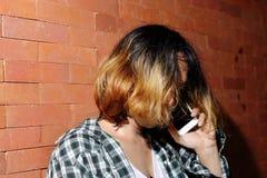 男女不分的美丽的年轻人画象作为谈一名美丽的妇女的在砖墙背景的流动巧妙的电话 免版税库存图片