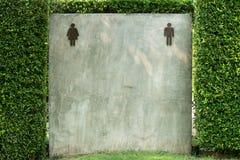 男女皆宜的公共厕所标志在灰色水泥墙壁上 免版税库存图片