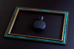 男女皆宜的香水特写镜头的黑表面无光泽的瓶在与金边界的鲜绿色框架里面在黑暗的背景,假装 免版税库存照片