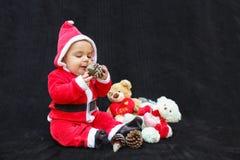 男婴在使用圣诞老人的衣服,黑背景 免版税库存照片