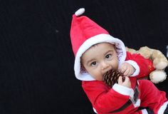男婴在使用圣诞老人的衣服,黑背景 库存图片