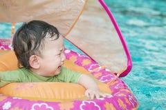 男婴在孩子的一条小船坐在恐惧情感的游泳池背景中的特写镜头 库存照片