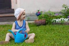 男婴坐绿草用蒲公英在庭院里开花在美好的夏日 免版税图库摄影
