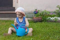 男婴坐绿草用蒲公英在庭院里开花在美好的夏日 免版税库存照片