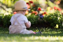 男婴坐草在美好的春天的庭院里 免版税库存图片