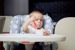 男婴奶油色吃酸奶 库存图片