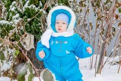 男婴惊奇与雪对冬景花园 图库摄影