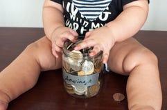 男婴拿着一个瓶子充满硬币 免版税图库摄影