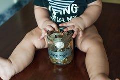 男婴拿着一个瓶子充满硬币 库存照片