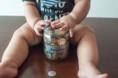 男婴拿着一个瓶子充满硬币 免版税库存照片