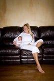 男婴母亲新出生的下个坐的沙发 库存照片