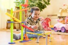 男婴演奏与一个创造性的多彩多姿的玩具 图库摄影