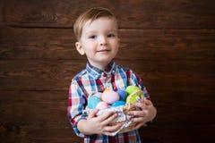 男婴用在篮子的复活节彩蛋在木背景 免版税库存图片