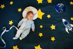 男婴睡着并且作自己空间的一位宇航员 免版税库存图片