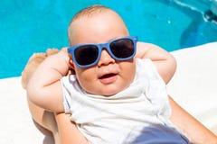 男婴获得与他的母亲的乐趣在蓝色水池 免版税库存照片