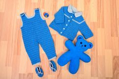 男婴蓝色说谎在地板上的冬天衣裳和鞋子 免版税库存图片