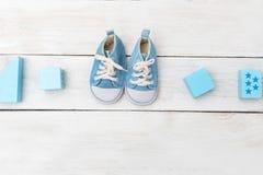 男婴鞋子和木玩具在木背景 平的位置 免版税图库摄影
