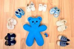 男婴鞋子在与玩具熊的一条线安排了 库存照片