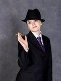 男子气概的样式的少妇与在灰色背景的微型人` s衣服和领带的雪茄,女孩,白色衬衣和帽子 库存图片