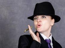 男子气概的样式的少妇与在灰色背景的微型人` s衣服和领带的雪茄,女孩,白色衬衣和帽子 库存照片