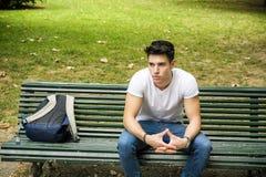 年轻男学生严重坐公园长椅 免版税库存图片