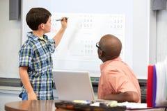 男学生在Whiteboard的文字答复 免版税库存照片