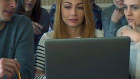男学生点他的在膝上型计算机屏幕上的铅笔 免版税库存照片