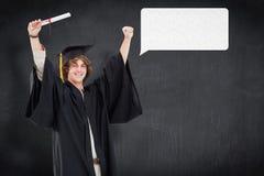 男学生的综合图象举他的胳膊的毕业生长袍的 免版税库存照片