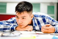 男学生研究在校园里|不耐烦和疲倦于考试 库存照片