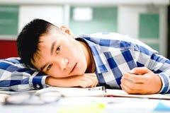 男学生研究在校园里|不耐烦和疲倦于考试 库存图片