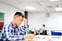 男学生研究在校园里|不耐烦和疲倦于考试 免版税图库摄影