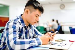 男学生研究在校园里|使用智能手机 库存照片