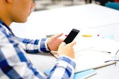 男学生研究在校园里|使用智能手机 库存图片