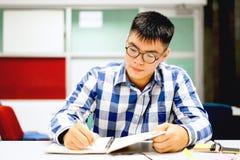 男学生研究在校园里|在做家庭作业的集中 免版税库存照片