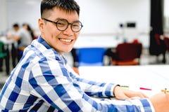 男学生研究在校园里|微笑和做家庭作业 免版税库存图片