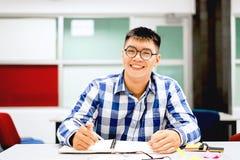 男学生研究在校园里|微笑和做家庭作业 免版税库存照片