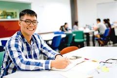 男学生研究在校园里|微笑和做家庭作业 库存照片