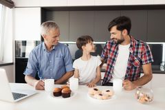 男孩、他的父亲和祖父在厨房里喝茶 在他们前谎言甜点 免版税库存照片