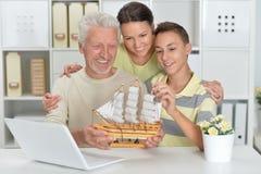 男孩、母亲和祖父画象有膝上型计算机和方式的 库存图片