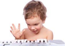 男孩一点钢琴作用 库存照片