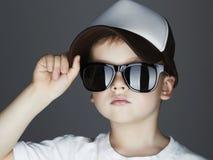 男孩一点 化妆舞会Soldier.Unusual制服 英俊在太阳镜和跟踪仪帽子 盖帽的孩子 免版税库存照片